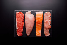 Group Of Animal Proteins, Chicken, Meat, Fish And Pork On A Black Background