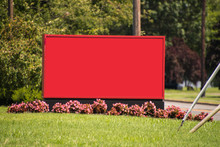 Large Blank Red Sign Board On Green Grass With Small Flowers At Its Base And Blurred Out Tree Background