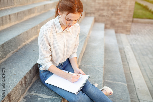 Fotografie, Obraz A beautiful young redhaired girl writes a romantic love letter sitting on a stairs near the institute