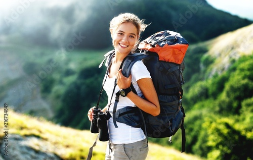 Obraz Woman with backpack trekking through the wilderness - fototapety do salonu