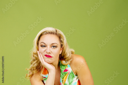 Valokuva  Portrait of a bored and unhappy blonde woman, isolated on green studio backgroun