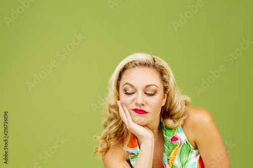 Photo Portrait of a grumpy blonde woman, isolated on green studio background