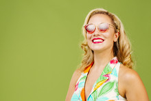 Smiling Blonde Woman With Red Sunglasses And Summer Dress, Isolated On Green Studio Background