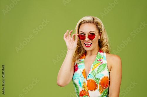 Fotografering  Beautiful blonde peeking from under sunglasses, isolated on green studio backgro