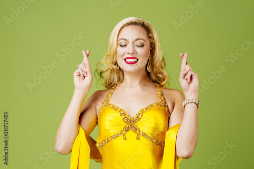 Fingers crossed, elegantly dressed blonde woman in yellow evening gown, isolated Canvas Print