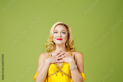 Photo  Dressed up blonde woman full of emotion, isolated on green studio background