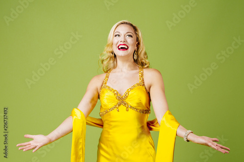 Enjoying the limelight, an elegant blonde with arms out, isolated on green studi Wallpaper Mural