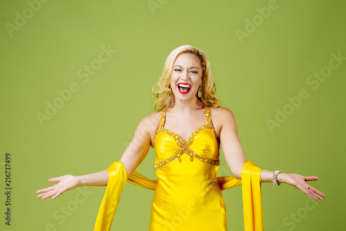 A very excited  blonde  in yellow evening gown with arms out, isolated on green Canvas Print
