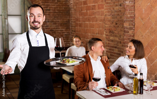 Fotografia Waiter showing country restaurant to visitors