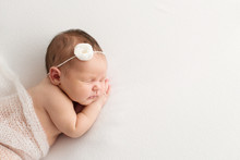 Sleeping Newborn Girl On A White Background. Photoshoot For The Newborn. 7 Days From Birth. A Portrait Of A Beautiful, Seven Day Old, Newborn Baby Girl