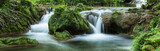 Panoramic view of small waterfalls streaming into small pond in green forest in long exposure