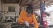 Young beautiful car mechanic repairing a car in a garage. car service concept.