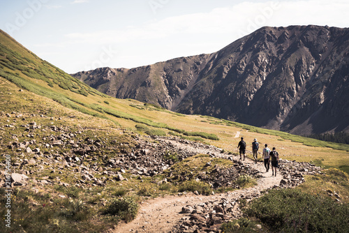 Foto op Canvas Beige Four people walking on a trail in the mountains of Colorado.