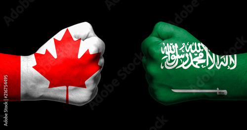 Staande foto Canada Flags of Canada and Saudi Arabia painted on two clenched fists facing each other on black background/Canada and Saudi Arabia relations concept