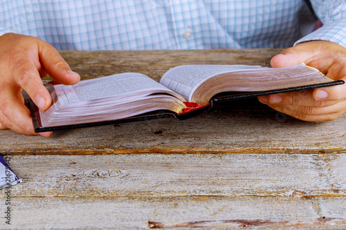 Fotografie, Obraz  A man reading the Holy Bible close up hands