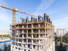 New Apartment Building Under Construction And Tower Crane Against Blue Sky Background. Drone Photo.