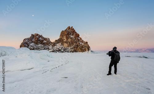 Foto op Plexiglas Asia land Travelling in winter, photographer carrying camera tripod at frozen lake Baikal in Siberia, Russia