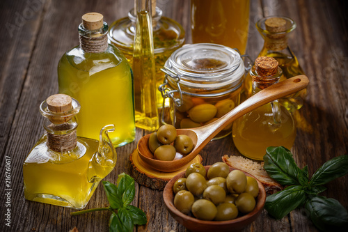 Foto op Plexiglas Aromatische Olive oil glass bottles with olive berries