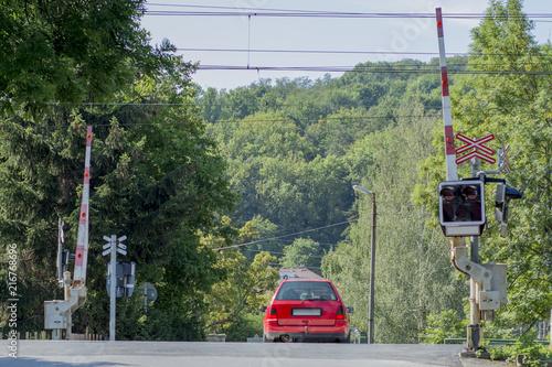 Fotografia, Obraz  Railroad crossing with barrier and a car