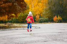 Girl In A Pink Jacket And Boots Running Through The Park In Autumn