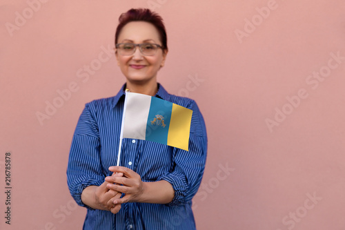 Deurstickers Canarische Eilanden Woman holding Canary Islands flag. Nice portrait of middle aged lady 40 50 years old with autonomous Canary Islands Spain flag. Visit Canary Islands concept.