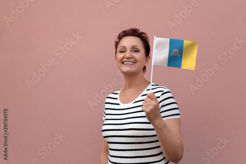 Tuinposter Canarische Eilanden Woman holding Canary Islands flag. Nice portrait of middle aged lady 40 50 years old with autonomous Canary Islands Spain flag. Visit Canary Islands concept.
