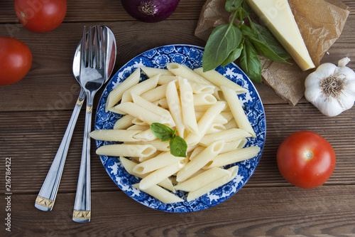 Foto op Plexiglas Gebakken Eieren Cooked penne pasta with butter,cheese and fresh vegetable ingredients on background: tomato, garlic, onion, fork and spoon, basil. Vintage beautiful blue plate on wooden table. Isolated.