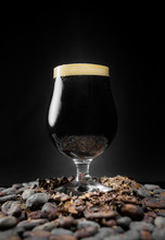 Dark Black Stout Beer Pint Over A Pile Of Cocoa Nibs And Beans
