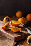 Fresh ripe persimmon on a wooden cutting board