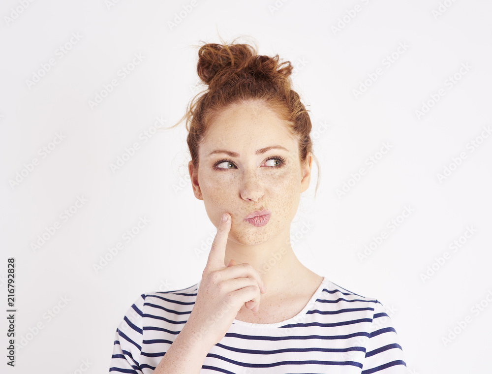 Fototapety, obrazy: Woman with hand on chin thinking at studio shot