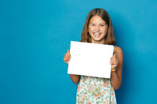 Beautiful Smiling Child (girl) With White Teeth Holding In Hands White Blank Copy Space For The Announcement