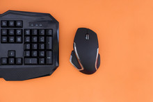 Workspace With A Keyboard And Mouse On A Orange Background. Copyspace. Black Mouse, Keyboard Isolated On A Orange Background, Top View. Flat Lay Gamer Background.
