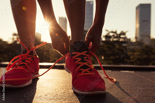 Fotografia  Fitness woman runner tying shoelace before running on city
