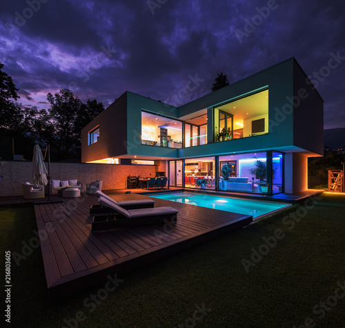 Photo  Modern villa with colored led lights at night