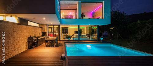 Valokuva  Modern villa with colored led lights at night