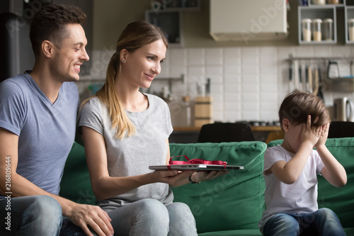 Loving Parents Mom And Dad Making Present To Kid Son Holding New Laptop Presenting As Gift Cute Child Boy Closing Eyes With Hands Waiting For Birthday