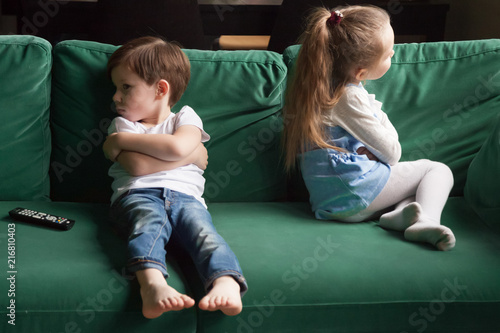 Photo Upset siblings boy and girl sulking sitting with arms crossed on sofa not talkin
