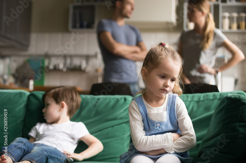 Photo  Upset little girl feeling sad after fight with brother sitting on sofa with worr