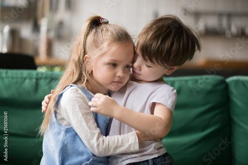 Fotografie, Obraz Little boy hugging consoling upset girl sitting on sofa, kid brother embracing s