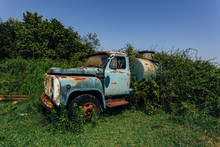 Old Rusty Overgrown Truck. Abandoned Soviet Tank Car In Ghost Town