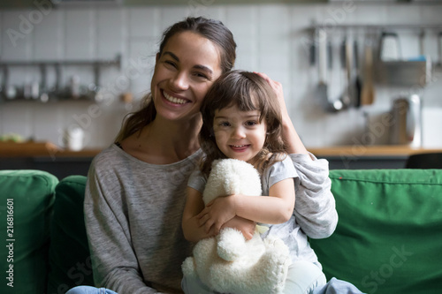 Fotografia Portrait of happy family single mother and kid daughter embracing on sofa at hom