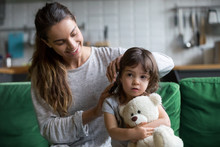 Young Loving Mother Brushing Kid Daughters Hair Sitting On Sofa, Smiling Single Mom Sister Helping Child Girl With Hairstyle At Home Getting Ready, Family Care, Morning Preparations Lifestyle Concept