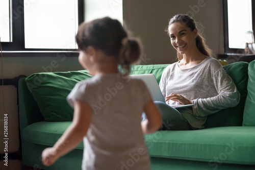Cuadros en Lienzo Smiling mother working online on laptop while kid daughter playing at home, youn