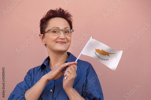 Foto op Canvas Cyprus Cyprus flag. Woman holding Cypriot flag. Nice portrait of middle aged lady 40 50 years old with a national flag over pink wall background.