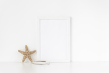 Minimal White Frame Mockup A4 In Interior With Sea Elements . Frame Mock Up Background For Bloggers, Social Media, Lettering, Art And Design. Indoor, Frame On Table. Summer Sea Mood