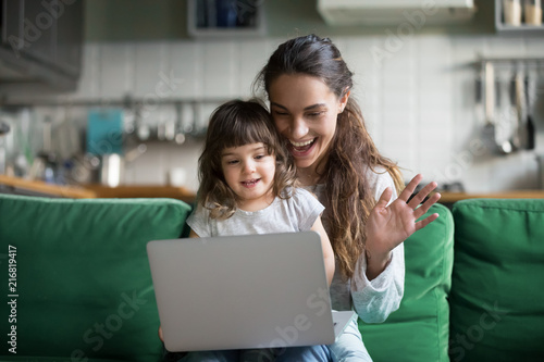 Happy mother and kid daughter waving hands looking at web camera using laptop for video call, smiling mom and child girl having fun greeting online by computer webcam making videocall via application