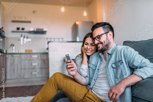 Obraz na plátně Close-up image of couple watching at smartphone screen indoors.