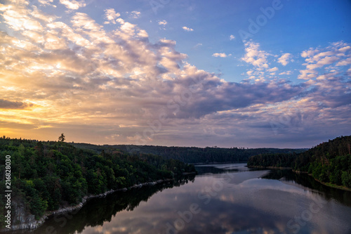 Colourful sunset over a lake. Summer scene of wide river landscape with setting sun.