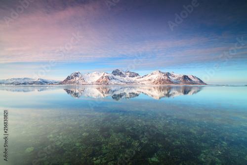 Snowy peaks reflected in the crystalline sea, Grundstad, Lofoten Islands, Norway