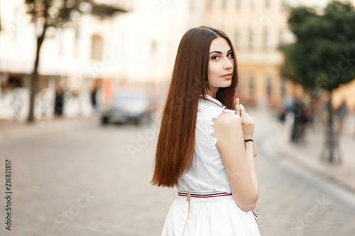 Fényképezés  Stylish young beautiful woman in white dress on the street